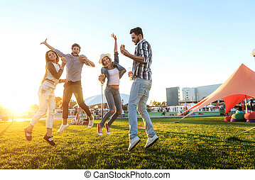 group of friends together in the park having fun - happy...