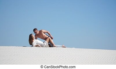 Muscular man and a beautiful girl lying on the sand in the...