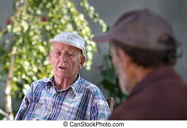 Two senior citizens chatting - Two senior men talking in...