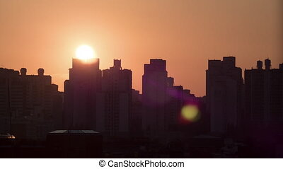 Time lapse shot of sun rising and moving in the sky, city modern buildings on the foreground. Seoul, South Korea