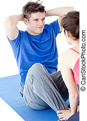 Young man doing fitness exercises with a woman