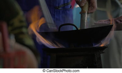 Cooking dish in wok on open fire, Thailand - Man cooking in...