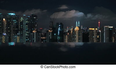 Night Kuala Lumpur, view from rooftop pool - Dark water of...