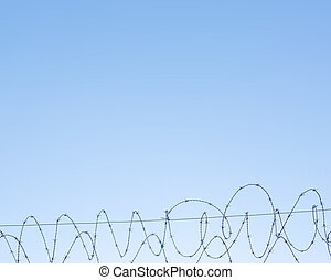 Barbed wire background - Barbed wire against blue sky,...