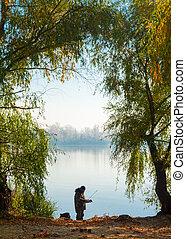 Autumn fishing - fisherman silhouette on the winter lake...