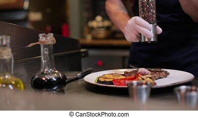 chef sprinkles seasoning grilled vegetables.