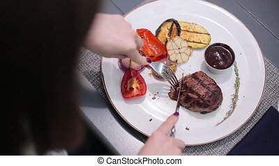 Woman cutting a steak on the plate