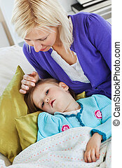 Sick cute child lying on couch in living room