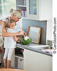 Concentrated mother and child cooking in kitchen