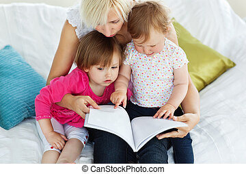 Cute mother reading a book with children