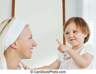 Smiling mother playing with her daughter
