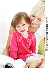 Smiling mother reading a book with children