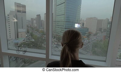 Woman working on business with pad by window with Seoul...
