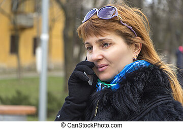 Attractive red-haired girl talking by phone outdoor -...