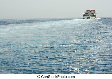Ferryboat is moving across sea and makes waves behind his...