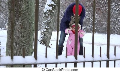 Mother and baby daughter having fun in winter park. 4K -...