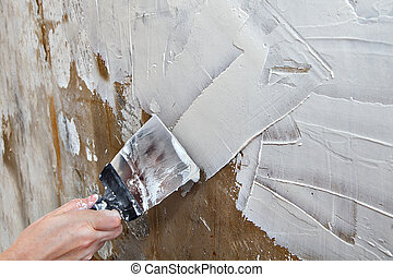 Aligning wall painters putty, painter hands holding steel...