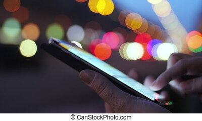 Texting sms on background of city and transport lights -...