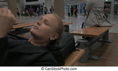 Woman waiting in airport lying on the bench with pad - Tired...