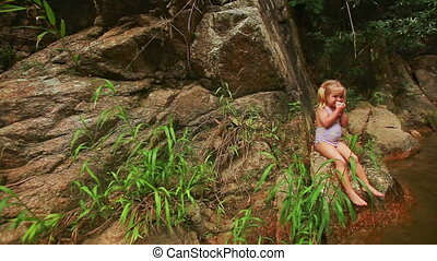 Little Girl with Pigtails Sits on Stone Bank Eats Fruit -...