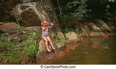Closeup Little Blond Girl Sits on Stone Bank Eats Fruit -...
