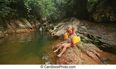 Little Girl in Arm-bands Sits on Stone Top Eats by River