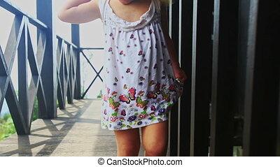 Little Blond Girl Runs Barefoot about Balcony among Legs -...
