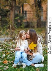 Mother kissing daughter. Baby shows tongue. - Family walk....