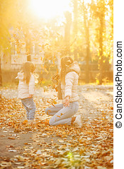 Mother and daughter throw up fallen leaves. Joy. - Family...