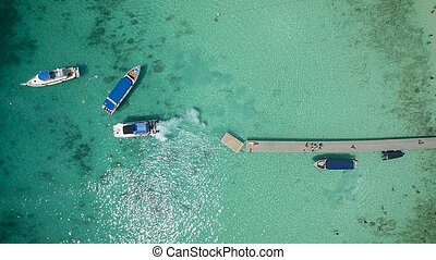 top view of speed boat approaching to jetty over clear blue...