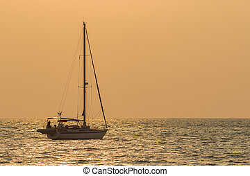 silhouette of sailing yacht boat floating over sun set sky...