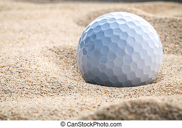 Close up golf ball in sand bunker shallow depth of field. A...