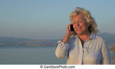 On the sea coast city of Perea, Greece is walking woman and talking on mobile phone