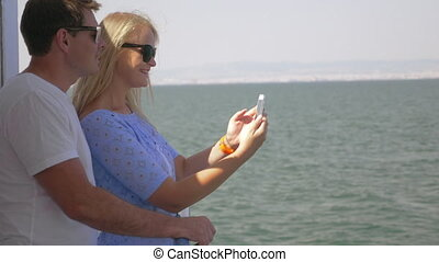 On sea in city of Perea, Greece on a ship young couple doing selfie on a mobile phone
