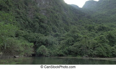 Close approach to mountain and cave by boat - View on...