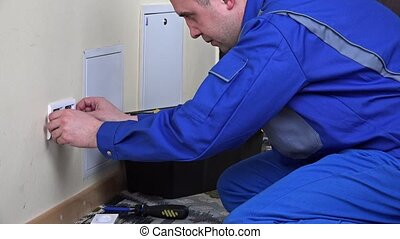 electrician man installing a wall power socket