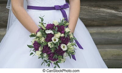 The bride holding a wedding bouquet - The bride dressed in...