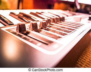 Keyboard of a synthesizer with sliders. Closeup of musical...