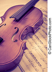 Old violin lying on the sheet of music, music concept