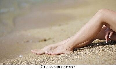 Womens beautiful smooth legs on white sand beach -...