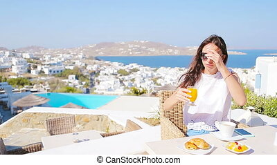Beautiful elegant girl having breakfast at outdoor cafe with amazing view on Mykonos town.