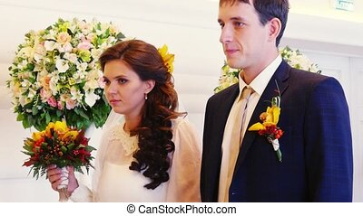 Handsome groom with beautiful bride at registry office....