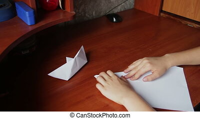 children's hands making origami plane