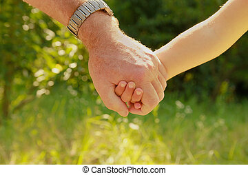 two hands of an elderly couple and child