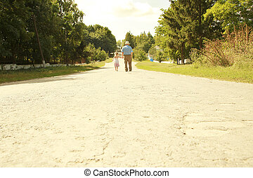Grandfather with granddaughter walk along the road,