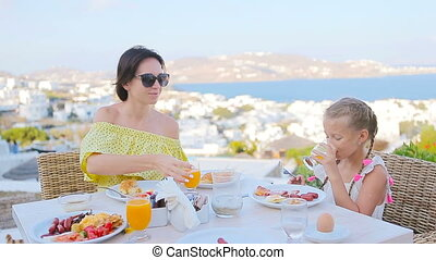 Family having breakfast at outdoor cafe with amazing view on...