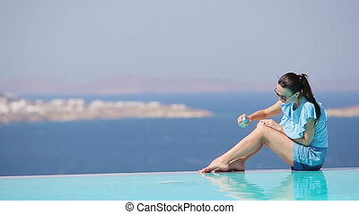 Slim woman applying sunscreen on her legs, sitting on the edge of pool background old town Mykonos in Europe