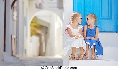 Two girls in blue dresses having fun outdoors Kids at street...