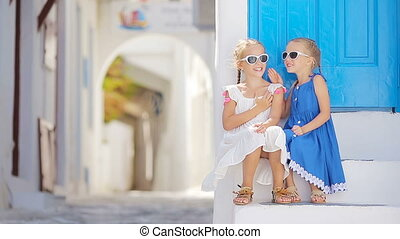 Cute little girls at street of typical greek traditional village with white walls and colorful doors on Mykonos Island, in Greece