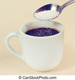 Sugar is poured from spoon in a coffee cup, gently toned -...